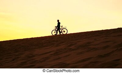 Silhouette of a man with his bike walking on sand dune, yellow sunset colors. 4K video