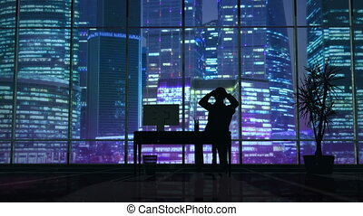 Silhouette of a man working late in the office at the computer