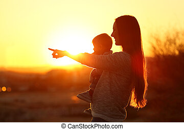Silhouette of a mother pointing horizon with her baby