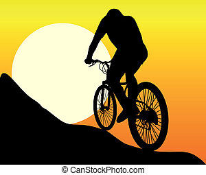 silhouette of a mountain biker in the sun and the orange sky...