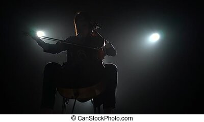 Silhouette of a musician with a cello in a dark studio with lanterns. Black smoke background