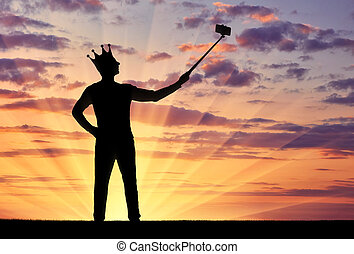 Silhouette of a narcissistic and selfish man with a crown on his head, makes selfie on the phone