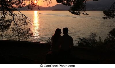 Silhouette of a newlywed couple at the sea at sunset. Wedding in