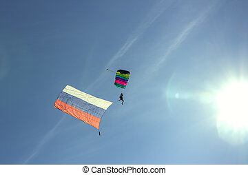 Silhouette of a parachutist flying in the sky to the sun