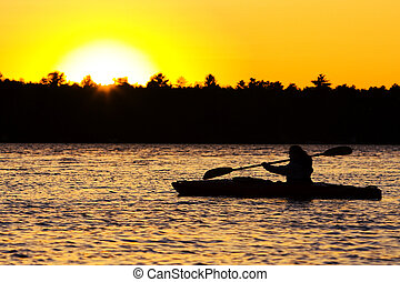Silhouette of a person kayaking on lake at sunset. Paddle is in mid-stroke.