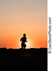 silhouette of a person running towards sunset sky background