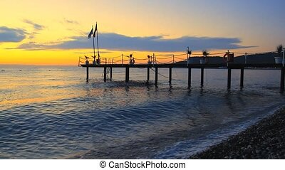 Silhouette of a pier with flag at sunrise on the sea in...