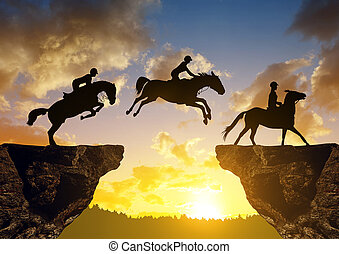 Silhouette of a rider on a horse jumping through the gap between rock
