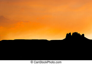 silhouette of a rock butte in the desert at sunset