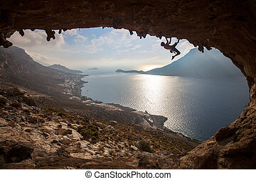 Silhouette of a rock climber against picturesque view of Telendos Island at sunset. Kalymnos Island, Greece.