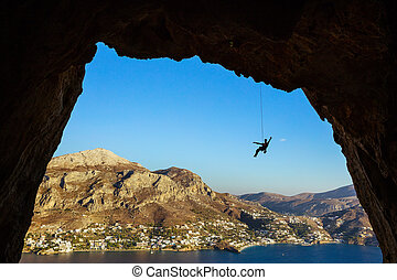 Silhouette of a rock climber hanging on rope while climbing in cave
