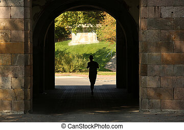 silhouette of a runner in the shadow of gates