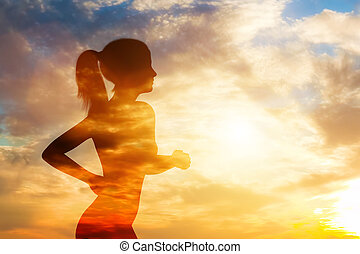 Silhouette of a running woman on sky background.