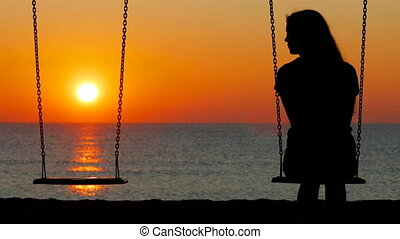 Silhouette of a sad girl swinging looking at side - Back ...