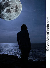 silhouette of a sad lone woman with a full moon on a cliff...