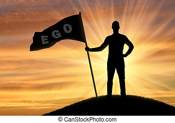 Silhouette of a selfish man with a crown on his head holds a flag with the word ego on top of a hill