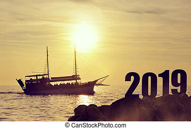Silhouette of a ship at sea in the sunset. New Year 2019 concept.