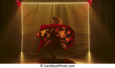 Silhouette of a slender attractive woman dancing in a gypsy costume. The woman is whirling in a dance swinging her skirt. A dark studio with soft yellow lights and smoke. Slow motion