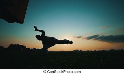 Silhouette of a strong man dancing capoeira at sunset, summer evening