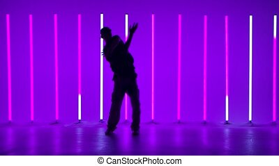 Silhouette of a stylish young man dancing and performing contemporary choreography. Street contemporary dance among bright flashing multicolored neon lights. Hip hop technique teaching concept. Youth subculture. Slow motion.
