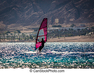 silhouette of a surfer in the Red Sea on the background of a rocky coast with palm trees and a hotel in Egypt Dahab