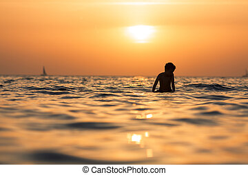 silhouette of a surfer on sunset background in the sea or ocean