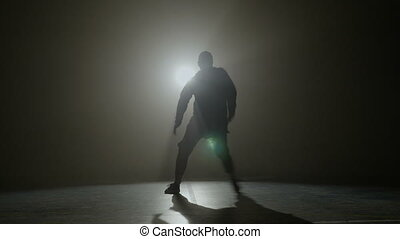 Silhouette of a talented young dancer dancing hip hop street...