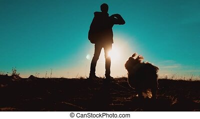 silhouette of a tourist and dog pet. Male tourist with dog stands on top man of a mountain. man silhouette at sunset. hikers adventure and the dog go walking. lifestyle travel mountains silhouette
