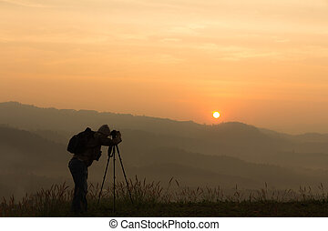 Silhouette of a traveler taking photo sunup in the mountains