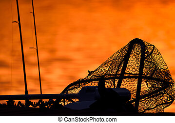 Silhouette of a trollingmotor, landing net and fishing rods