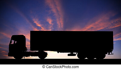 Silhouette of a truck on road at sunset