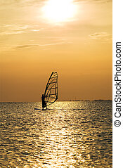 Silhouette of a windsurfer on a sunset
