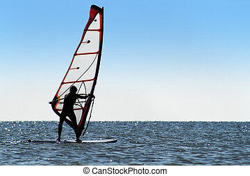 Silhouette of a windsurfer on the blue sea surface