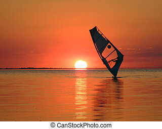 Silhouette of a windsurfer on waves of a gulf on a sunset 1
