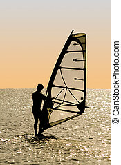 Silhouette of a windsurfer on waves of a gulf