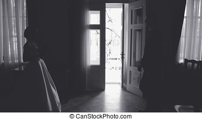 Silhouette of a woman against a light window, a wedding in black and white