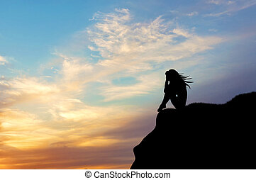 Silhouette of a woman alone on a hill at sunset - Loneliness...