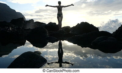 Silhouette of a woman at sunset observing waves and raising arms in the air. Cinematic slow motion