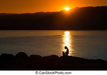 Silhouette of a woman doing yoga on the beach at sunset