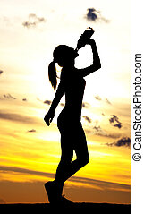 woman drinking water - Silhouette of a woman drinking water...