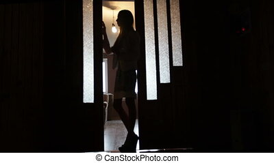 Silhouette of a woman in a doorway