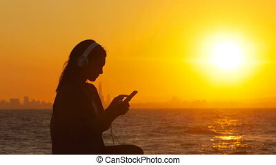 Silhouette of a woman listening to music at sunset -...