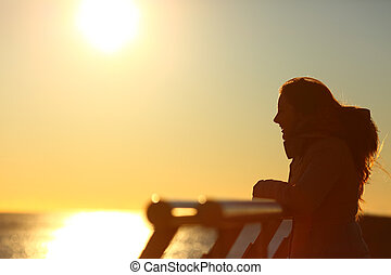 Silhouette of a woman looking at horizon at sunset