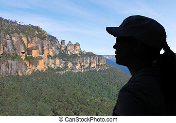 Silhouette of a woman looks at the landscape