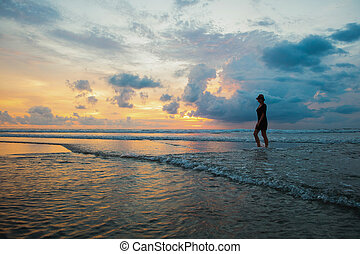 Silhouette of a woman on the background of beautiful sunset on the Kuta beach