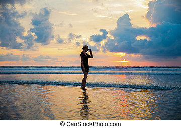 Silhouette of a woman on the background of sunset on the Kuta beach