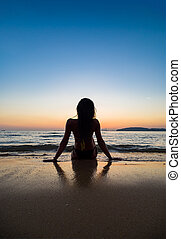 Silhouette of a woman on the beach at sunset