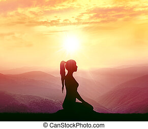 Silhouette of a woman practicing yoga in the mountains