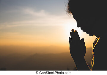 silhouette of a woman Praying hands with faith in religion and belief in God On the morning sunrise background. Namaste or Namaskar hands gesture, Pay respect, Prayer position.
