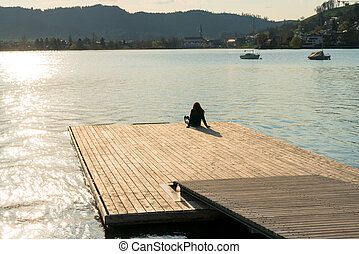 silhouette of a woman relaxing on a floating dock on a lake at sunset